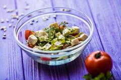 Smaklig ny sallad och tomate på den purpurfärgade trätabellen Mat Arkivbild