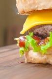 Smaklig ostburgare med grönsallat, nötkött, dubbel ost och ketchup Arkivfoto