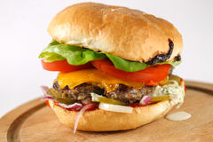 Smaklig ostnötkötthamburgare med grönsallat, cheddar och tzatziki Fotografering för Bildbyråer