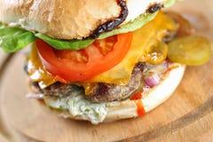 Smaklig ostnötkötthamburgare med grönsallat, cheddar och tzatziki Arkivfoto