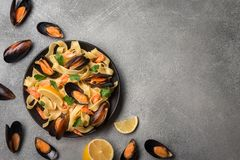 Smaklig pasta med musslor, tioarmade bläckfisken, persilja och citronen, bästa sikt arkivbild