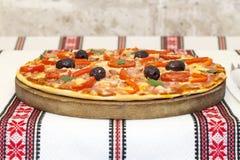 Smaklig pizza med grönsaker, basilika, oliv, tomater, paprika på skärbrädan, traditionellt färgrikt för tabelltorkduk Royaltyfri Foto