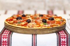 Smaklig pizza med grönsaker, basilika, oliv, tomater, paprika på skärbrädan, traditionellt färgrikt för tabelltorkduk Arkivbilder