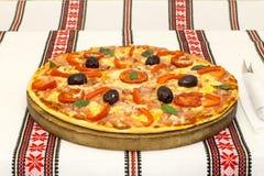 Smaklig pizza med grönsaker, basilika, oliv, tomater, paprika på skärbrädan, traditionellt färgrikt för tabelltorkduk Arkivbild