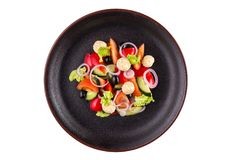 Smaklig sallad med tioarmade bläckfisken, grönsaker och apelsin, klädde med sås på en svart platta Sallad i en platta som isolera Fotografering för Bildbyråer