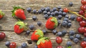 Smaklig sommar bär frukt på en trätabell Video för hd för ULTRARAPID för björnbär för blåbärdruvajordgubbar arkivfilmer