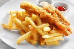 Smaklig stekt fisk, chiper och såser på plattan royaltyfri fotografi
