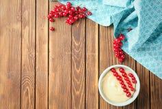 Smaklig vaniljpudding med den röda vinbäret i ramekin arkivfoto