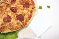 Smaklig varm pizza med korvost och den vita klistermärken royaltyfria foton