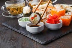 Smakliga aptitretande mångfärgade sushirullar ställde in, tjänat som med soya och pinnar arkivfoton