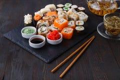 Smakliga aptitretande mångfärgade sushirullar ställde in, tjänat som med soya och pinnar fotografering för bildbyråer