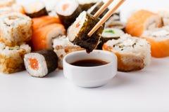 Smakliga aptitretande mångfärgade sushirullar ställde in, tjänat som med soya och pinnar arkivbilder