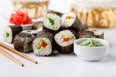 Smakliga aptitretande mångfärgade sushirullar ställde in, tjänat som med soya och pinnar arkivbild
