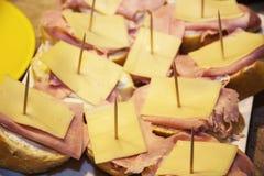 Smakliga canapes med ost, skinka och smör arkivfoto