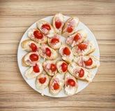 Smakliga canapes med smör, skinka och körsbärsröda tomater, full vit p royaltyfria bilder