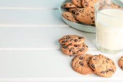 Smakliga choklade kakor och exponeringsglas av mjölkar på trätabellen arkivbilder