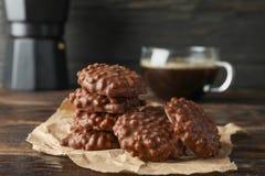 Smakliga chokladkakor med koppen kaffe på trätabellen arkivbild