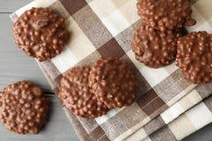 Smakliga chokladkakor på servett och träbakgrund arkivfoto