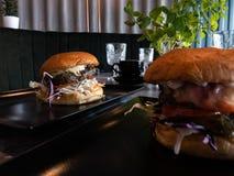 Smakliga enorma hamburgare i en restaurang - på en tabell royaltyfri bild