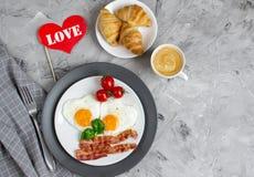 Smakliga Fried Egg i Shape av en hjärta som tjänas som på en vit platta med bacontomaten Basil Pepper fotografering för bildbyråer