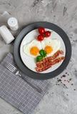Smakliga Fried Egg i Shape av en hjärta som tjänas som på en vit platta med bacontomaten Basil Pepper arkivbilder