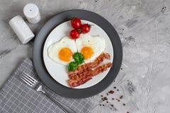 Smakliga Fried Egg i Shape av en hjärta som tjänas som på en vit platta med bacontomaten Basil Pepper royaltyfria foton