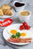 Smakliga Fried Egg i Shape av en hjärta som tjänas som på en vit platta med bacontomaten Basil Pepper royaltyfri fotografi
