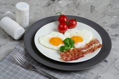 Smakliga Fried Egg i Shape av en hjärta som tjänas som på en vit platta med bacontomaten Basil Pepper royaltyfria bilder