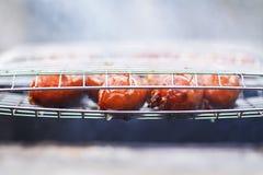 smakliga grillade korvar Steka på fyrpanna utomhus i bygden på sommar royaltyfri foto