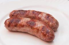 Smakliga grillade köttkorvar på maträtt Royaltyfria Bilder
