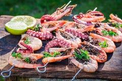 Smakliga grillade steknålar av skaldjur med citronen och persilja Royaltyfri Bild