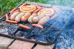 Smakliga griskött- och nötköttkorvar som lagar mat över de varma kolen Royaltyfri Bild
