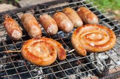 Smakliga griskött- och nötköttkorvar som lagar mat över de varma kolen Arkivbilder