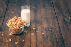 Smakliga havreflingor i bunke med exponeringsglas av mjölkar Royaltyfri Foto