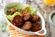 Smakliga köttbullar och grönsaker på plattan Royaltyfria Bilder