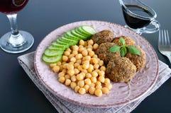 Smakliga köttkotletter, kikärtar, ny gurka på en keramisk platta och ett exponeringsglas av vin fotografering för bildbyråer