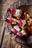 Smakliga kalla mellanmål med nya ingredienser i träbunke Royaltyfri Foto