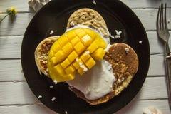 smakliga ljusa sunda frukost-pannkakor, yoghurt och mango Arkivfoton