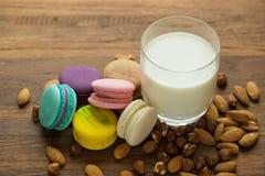 Smakliga makron och koppen av mjölkar med mandeln på träbakgrund fotografering för bildbyråer