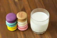 Smakliga makron och koppen av mjölkar med mandeln på träbakgrund royaltyfria bilder