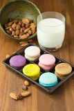 Smakliga makron och koppen av mjölkar med mandeln på träbakgrund royaltyfri foto