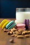 Smakliga makron och koppen av mjölkar med mandeln på träbakgrund royaltyfria foton