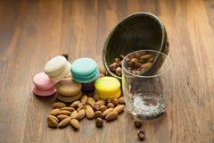 Smakliga makron och koppen av mjölkar med mandeln på träbakgrund arkivbilder