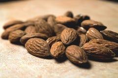 Smakliga mandlar som är tokiga på träbakgrund Royaltyfri Bild