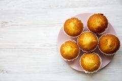 Smakliga muffin på rosa färgrundaplattan över vit träyttersida ovanför sikt royaltyfria bilder