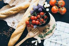 Smakliga nya tomater i en stylissvartmaträtt med läckert bröd som ligger på träskärbrädan som är klar för att laga mat och Arkivbilder