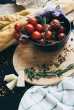 Smakliga nya tomater i en stylissvartmaträtt med läckert bröd som ligger på träskärbrädan som är klar för att laga mat och Fotografering för Bildbyråer
