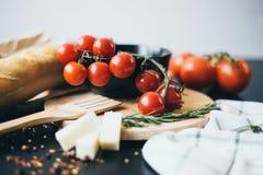 Smakliga nya tomater med läckert bröd som ligger på träskärbrädan som är klar för att laga mat och framställning av fantastiskt m Arkivfoto