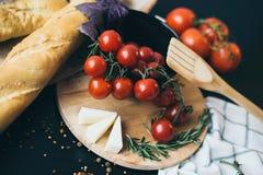 Smakliga nya tomater med läckert bröd som ligger på träskärbrädan som är klar för att laga mat och framställning av fantastiskt m Royaltyfri Bild