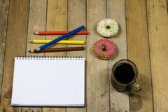 Smakliga och nya donuts och en anteckningsbok, blyertspennor för att dra Sket Royaltyfria Foton